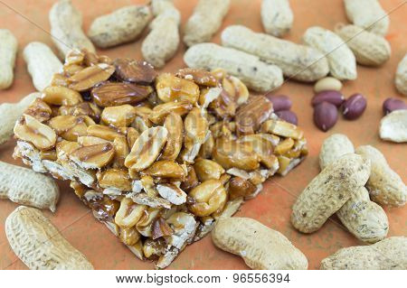 Honey Bar With Peanuts Almonds And Hazelnuts Surrounded By Roasted And Raw Peanuts On A Orange Backg