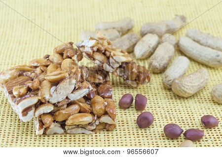 Honey Bar With Peanuts Almonds And Hazelnuts Surrounded By Roasted And Raw Peanuts On A Yellow Backg