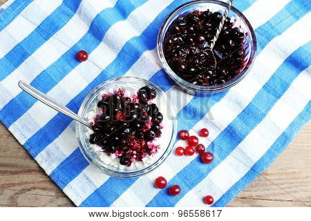 Cottage cheese with black canned currant on striped napkin, top view
