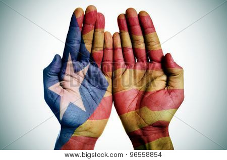the hands of a man patterned with the Estelada, the Catalan pro-independence flag