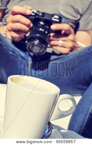 closeup of a young man checking his camera while he es taking a coffee in the terrace of a bar