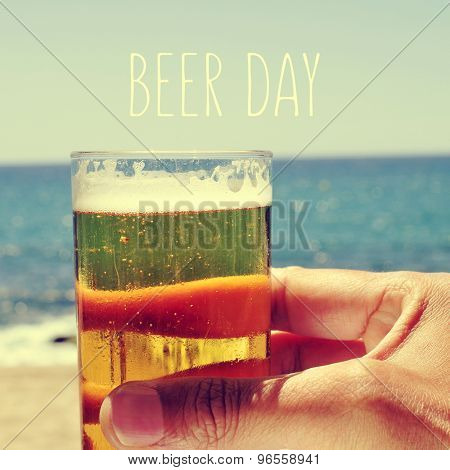 closeup of the hand of a man with a refrehing beer near the sea and the text beer day