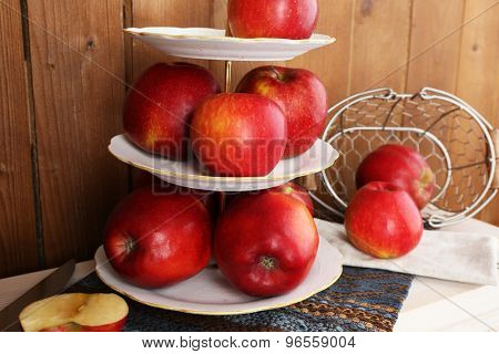 Tasty ripe apples on serving tray on wooden background