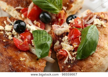 Pieces of homemade pizza on plate, close-up