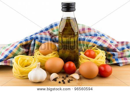 Pasta Nests, Eggs, Tomatoes, Garlic And Oil Bottle On Board