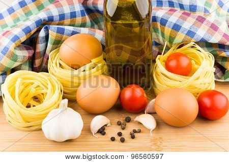 Pasta Nests, Eggs, Tomatoes And Oil On Background Of Towels