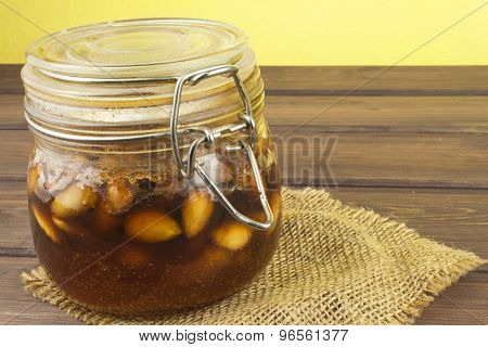 Jar of honey and nuts. Sweet treat for snacking. Pickled walnuts in honey.
