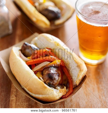 grilled bratwursts with onions and peppers in brown paper tray