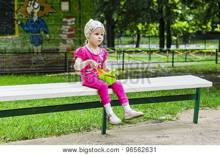 Little Girl Sitting On The Bench With A Book