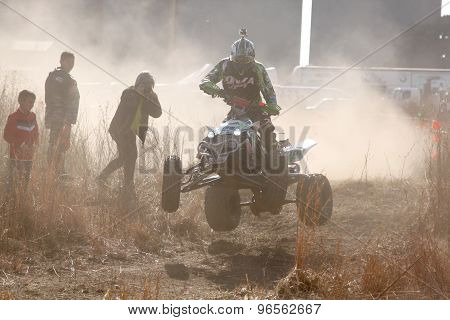 Quad Bike Airborne Over Hump In Trail Of Dust On Sand Track During Rally Race.