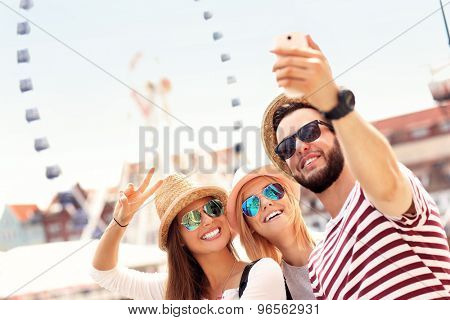 A picture of a group of friends hanging out in the city and taking selfie