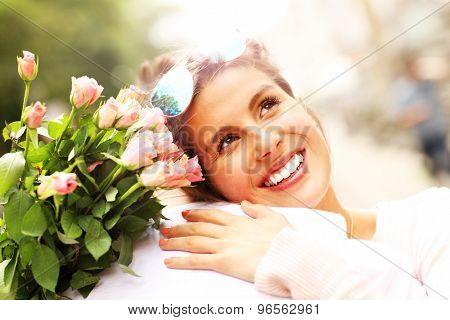 A picture of a pretty woman holding flowers and hugging a man