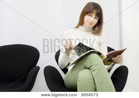 young caucasian woman sitting in the waiting room for doctors