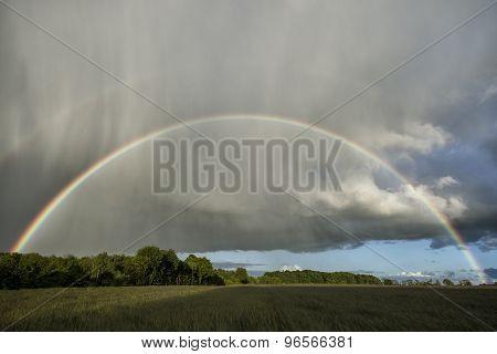 Double Rainbow Over A Field With Sunshine And Rain