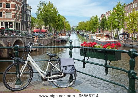 White Bicycle On A Bridge Overlooking A Canal In Amsterdam Against Blue Sky