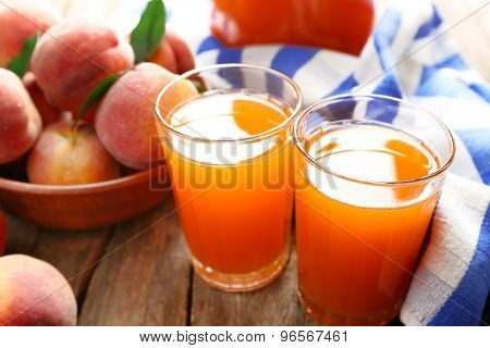 Ripe peaches and juice in glass on wooden background