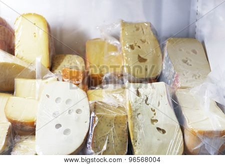 Set of cheese in plastic bags on shelf of fridge