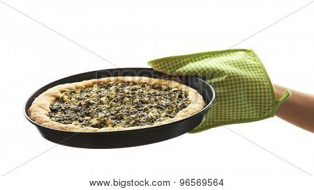 Hand holding open pie with spinach isolated on white