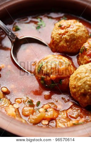 Meat balls with tomato sauce and wooden spoon, close-up