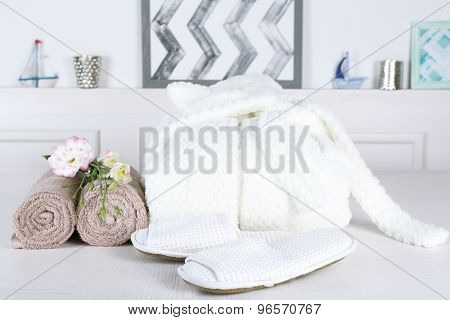 Bathrobe, towels and slippers on table, indoors