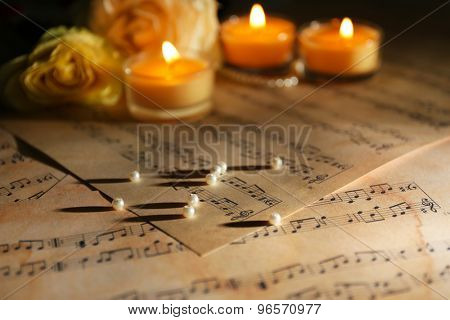 Beautiful rose with pearls and candles on music sheets, closeup