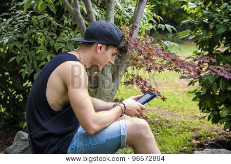 Young Man with Tablet or Ebook Reader Relaxing at Park