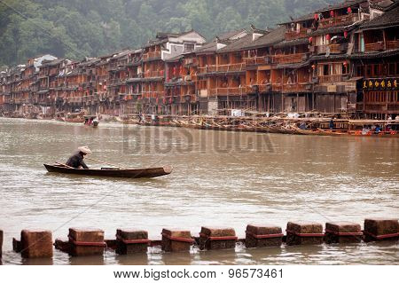Worker Paddle On The River Every Day In Fenghuang Ancient City.