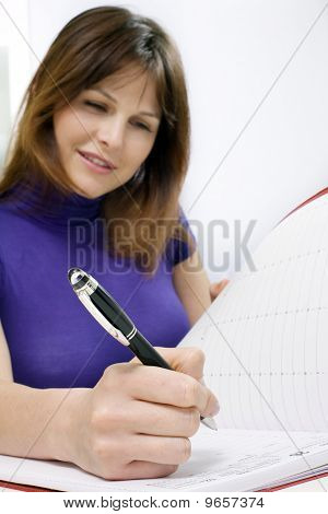woman working in a medical office with calendar of appointments