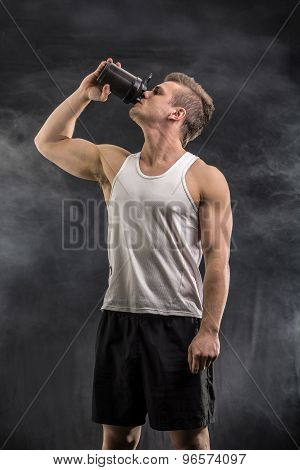 Attractive young man holding protein shake bottle.