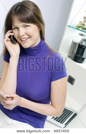 woman with mobile holding health card and booking medical exam