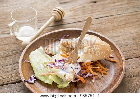 Piece Of Hotdog Remains On Wooden Plate