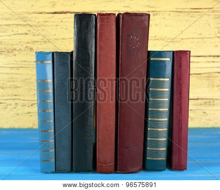 Retro books on yellow wooden background