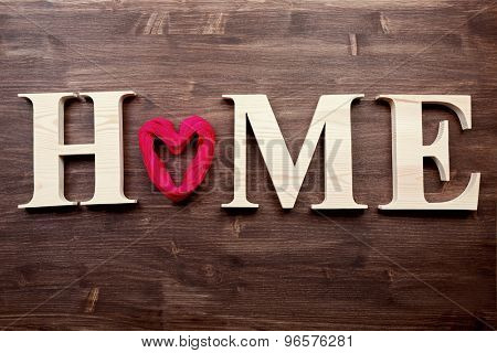 Decorative letters forming word HOME with heart on wooden background