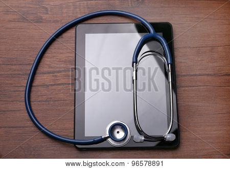 Stethoscope and tablet on wooden background