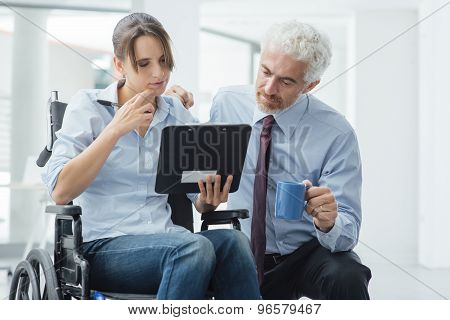 Businessman Showing A Document To A Woman In Wheelchair