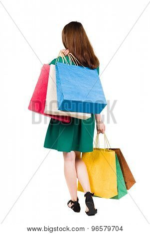 back view of going  woman woman with shopping bags. beautiful brunette girl in motion.  girl in stylish green dress standing with a bunch of multi-colored packages in different hands.