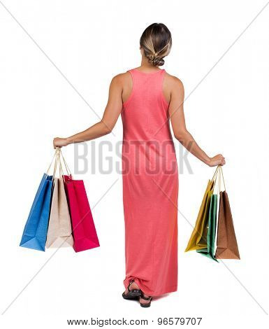 back view going woman in dress woman with shopping bags . beautiful brunette girl in motion.  Isolated over white background. girl in light red dress standing holding a plurality color shopping bags