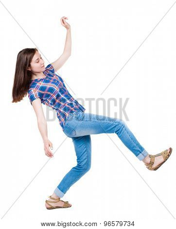 Balancing young woman.  or dodge falling woman. Rear view people collection.  backside view of person.  A young girl in a checkered blue with red stripes makes a great step forward.