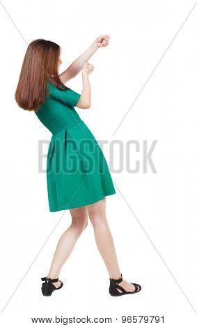 back view of standing girl pulling a rope from the top or cling to something. girl  watching.  Isolated over white background. The girl in stylish green dress pulling a rope from the top-right.