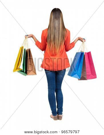 back view of going  woman  in  jeans woman with shopping bags . beautiful girl in motion.   Isolated over white background. Girl in a red jacket holding a raised hand colored shopping bags.