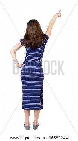 Back view pointing woman. beautiful girl. Rear view people collection.  backside view of person.  Isolated over white background. Girl in a blue striped dress standing and shows his right hand to sky.