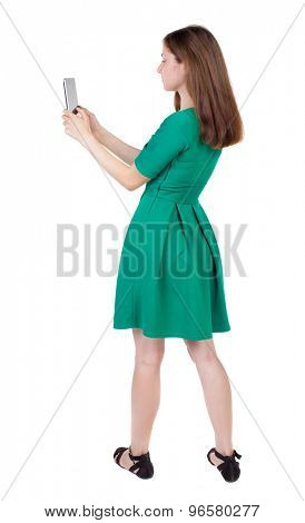 back view of standing young beautiful  girl with tablet computer in the hands of. girl  watching.  Isolated over white background. The girl in stylish green dress pictures of something on the tablet.