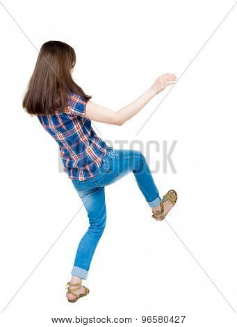 Back view woman Balances waving his arms.   Standing young girl in jeans. Rear view people collection. Isolated over white background. A young girl in a checkered blue with red stripes on back falling