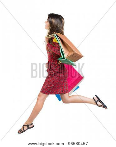 side view of a woman jumping with shopping bags. beautiful brunette girl in motion.    Isolated over white background. Long-haired girl in a red plaid dress jumping with colored paper bag.