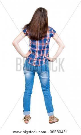 back view of standing young beautiful  woman.  girl  watching. Rear view people collection.  Isolated over white background. A young girl in a checkered blue shirt is resting in the palm of her waist.