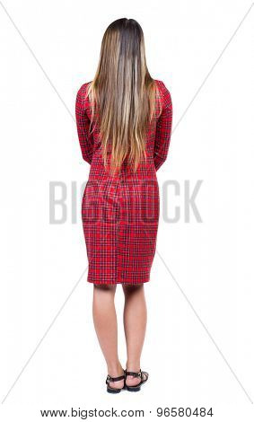 back view of standing young beautiful  woman.  girl  watching. Rear view people collection.   Isolated over white background.  Long-haired girl in a red plaid dress standing with his arms crossed.