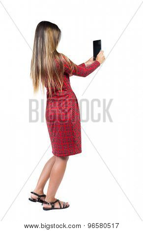 back view of standing young beautiful  girl with tablet computer in the hands of. girl  watching. Isolated over white background. Long-haired girl in a red plaid dress takes tablet something.