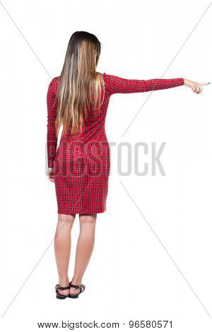 Back view of  pointing woman. beautiful girl. Rear view people collection.  backside view of person.   Long-haired girl in a red plaid dress is pointing in the right hand side.