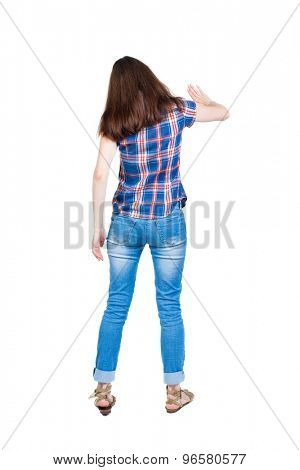 back view young woman presses down on something. Isolated over white background. Rear view people collection. backside view person. A young girl in checkered blue with red stripes hand presses button.