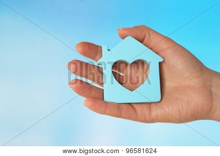 Female hand with model of house on color background